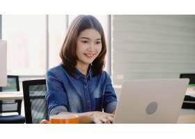 通过笔记本电脑在办公室工作的职业亚裔女商_4691904