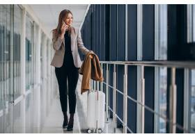 航站楼里的女商人提着旅行包打电话_7200185