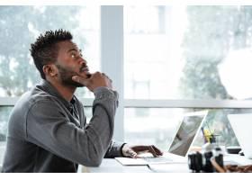 英俊思考严肃的年轻人坐在办公室一起工作_8078122