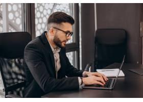 英俊的商务人士在电脑上工作_13377025