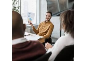 面带微笑的人在会议上向他的同事们展示一些_12065570