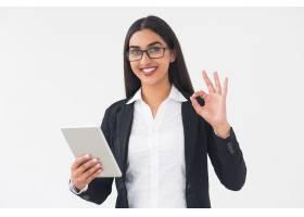 面带微笑的优雅女子手持平板电脑显示OK_1027123
