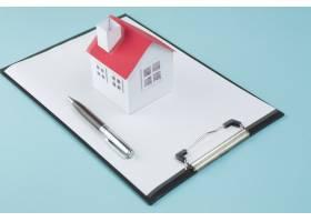 蓝色背景上空白剪贴板上的小房子模型和钢笔_5060985
