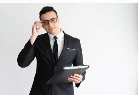 认真帅气的年轻商人调整眼镜拿着文件夹_2791174