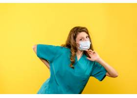 黄墙上戴口罩的女医生的正视图_13437277
