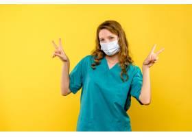 黄墙上戴口罩的女医生的正视图_13437321