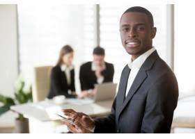 黑人商人在会议上使用数字平板电脑_3955632