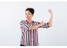 身着条纹衬衫的成熟女性展现出力量的手势_13401824