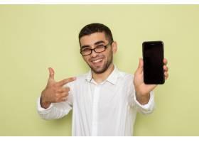身穿白色衬衫的男性上班族在绿色墙上微笑着_11982347