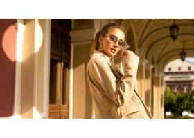 身穿米色外套的现代漂亮女孩站在室外的大楼_11953532