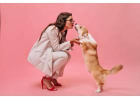身穿米色服装的美女在粉色背景下与狗玩耍_13211982