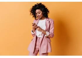身穿粉色夹克的微笑女子发短信_12860247