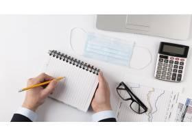 男子在财务元素旁边的空白记事本上写字_11621162