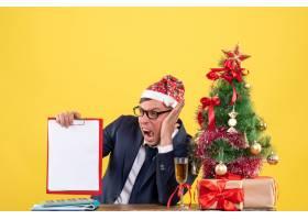 正面怒气冲冲的商人坐在圣诞树附近的桌子旁_13361377