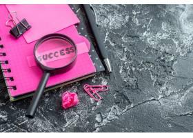 正面近景粉色记事本带笔放大镜和灰色背景_13291728