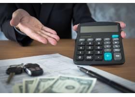 汽车销售员拿着钥匙在经销商办公室计算价格_1203165