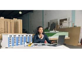 沉思的非裔美国女士手持笔记本电脑和建筑模_3706693