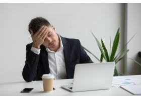 沮丧的千禧一代商人因为工作笔记本电脑而_3952553