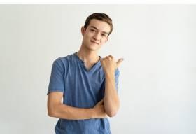 满意的穿着蓝色T恤的英俊年轻男子指着一边_3799048