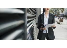 站在办公室外拿着文件夹和手机的年轻女商人_3681696