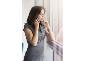 站在窗边拿着电话的女人_13274192
