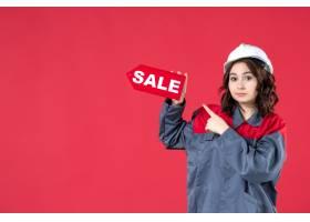 穿着制服的女工头戴安全帽在孤立的红色墙_12956808