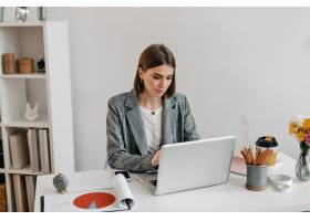 穿着灰色夹克的女商人在笔记本电脑上工作_11932512