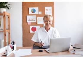 穿着白衬衫的女商人坐在她的办公室里_13013829