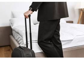 特写一位身穿黑色西装的时髦商人手持行李箱_9029233