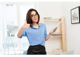 穿蓝色衬衫和黑色裙子的黑发女孩正站在办公_10015443