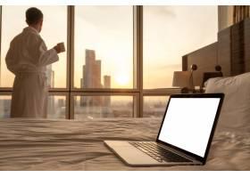 笔记本电脑在床上与身着浴袍的男子的特写镜_929384