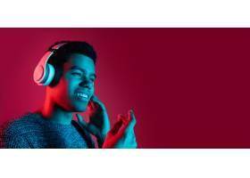 红色工作室墙上五颜六色霓虹灯下的男子肖像_12648043