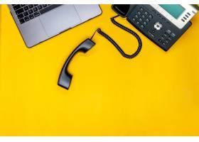 电话笔记本电脑平放工作空间在黄色背景_9658560