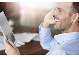 男人打电话和浏览数字平板电脑_13274119