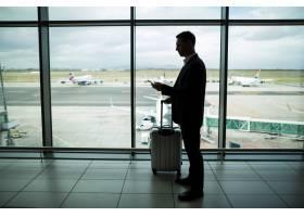携带行李的商人使用手机_10748351