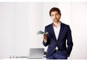 时髦成功的年轻商人在他的办公室里靠在桌_9226903