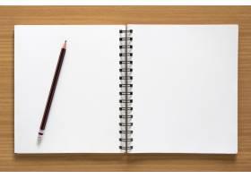 木质背景上的空白螺旋记事本和铅笔_1163970