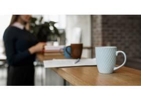桌子柜台上咖啡杯与散焦的女人的正视图_12065474
