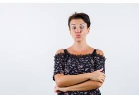成熟的女人双臂交叉站立嘴唇弯曲斜视着_13400716