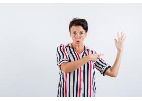 成熟的女人穿着条纹上衣指着停车的标志_13401533
