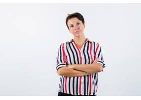 成熟的女人站着双臂交叉穿着条纹衬衫_13401835