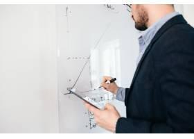 戴眼镜的年轻黑发男子在白板上写商业计划的_9961005