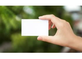 手持背景散焦的白纸_978428
