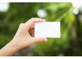 手持背景散焦的白纸_978430
