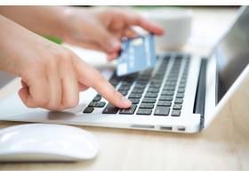 手持信用卡和笔记本电脑_978447
