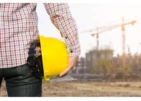 手持黄色安全帽的工程师有建筑现场背景_1287089