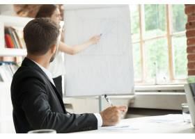 年轻的商人看着黑板上的工作流程图_3938104