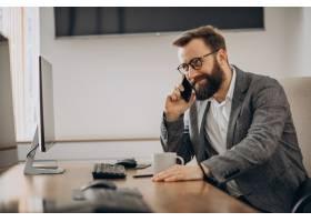 年轻的生意人在电话里聊天在电脑上工作_11601437