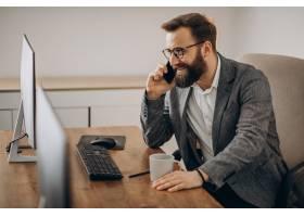 年轻的生意人在电话里聊天在电脑上工作_11601440