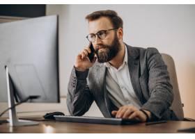 年轻的生意人在电话里聊天在电脑上工作_11601444